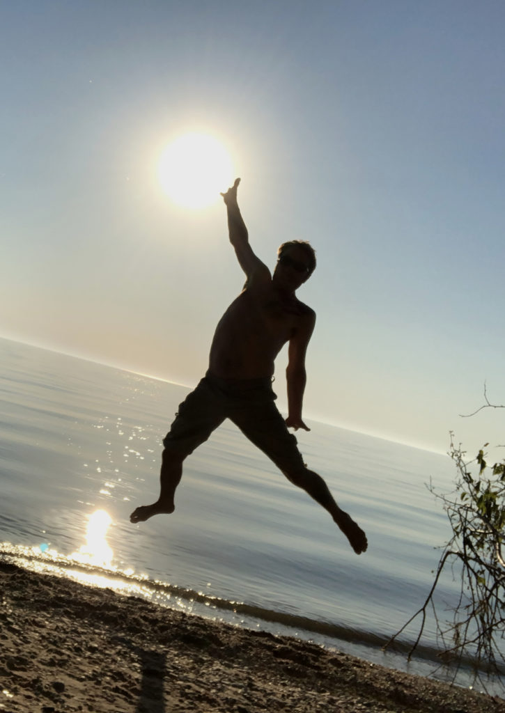 image of brian jumping on a beach