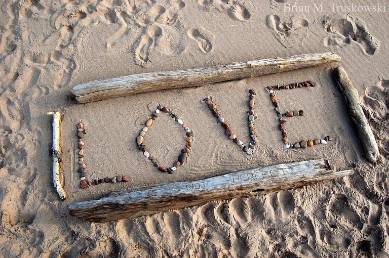 image of the word love written in stones and driftwood